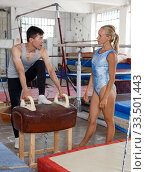 Купить «Man and woman doingexercises on pommel horse», фото № 33501443, снято 18 июля 2018 г. (c) Яков Филимонов / Фотобанк Лори