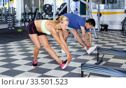 Купить «Portrait of young athletic couple practicing stretch exercises in fitness center», фото № 33501523, снято 16 июля 2018 г. (c) Яков Филимонов / Фотобанк Лори