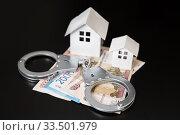 Деньги, наручники и дома на темном фоне. Мошенничество на рынке жилья. Стоковое фото, фотограф Наталья Осипова / Фотобанк Лори