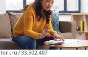 Купить «asian woman with papers and calculator at home», видеоролик № 33502407, снято 26 марта 2020 г. (c) Syda Productions / Фотобанк Лори