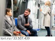 Guy enjoying conversation with woman in subway train. Стоковое фото, фотограф Яков Филимонов / Фотобанк Лори