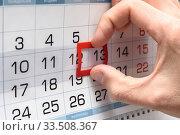Купить «Рука на календаре передвигает указатель с двенадцатого на тринадцатое число», фото № 33508367, снято 7 апреля 2020 г. (c) Иванов Алексей / Фотобанк Лори