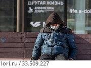 Купить «Мужчина в медицинской маске отдыхает на лавочке в центре города Москвы во время эпидемии коронавируса COVID-19 в России», фото № 33509227, снято 7 апреля 2020 г. (c) Николай Винокуров / Фотобанк Лори