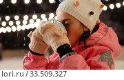 Купить «girl drinking hot tea on skating rink in winter», видеоролик № 33509327, снято 22 марта 2020 г. (c) Syda Productions / Фотобанк Лори