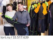 Купить «Woman seller helping man choose new costume for diving», фото № 33517639, снято 25 января 2018 г. (c) Яков Филимонов / Фотобанк Лори
