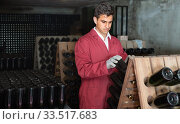 Man winery working in aging section with bottle racks in cellar. Стоковое фото, фотограф Яков Филимонов / Фотобанк Лори