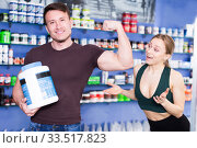 guy with sports nutrition and showing a muscle to a girl. Стоковое фото, фотограф Яков Филимонов / Фотобанк Лори