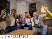 Купить «friends or soccer fans with ball and beer at home», фото № 33517903, снято 28 декабря 2019 г. (c) Syda Productions / Фотобанк Лори
