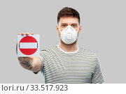 Купить «man in respirator mask showing stop sign», фото № 33517923, снято 21 марта 2020 г. (c) Syda Productions / Фотобанк Лори