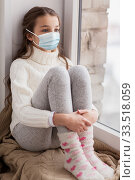 sad girl in medical mask sitting on sill at home. Стоковое фото, фотограф Syda Productions / Фотобанк Лори