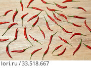 Pods of red chili peppers laid out on a wooden surface for drying. Стоковое фото, фотограф Евгений Харитонов / Фотобанк Лори