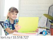 Купить «Девочка сидит за столом и счастливо смотрит в экран планшетного компьютера», фото № 33518727, снято 9 апреля 2020 г. (c) Иванов Алексей / Фотобанк Лори