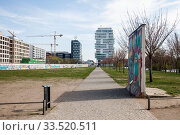 Wall strip at the East-Side-Gallery in Muehlenstrasse in Berlin-Friedrichshain, in the background the new office buildings at Mercedes-Platz and the Living Levels Project (2019 год). Редакционное фото, агентство Caro Photoagency / Фотобанк Лори