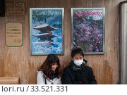 Kyoto, Japan, couple sitting at a bus stop in front of billboards with the slogan I Love Kyoto (2017 год). Редакционное фото, агентство Caro Photoagency / Фотобанк Лори