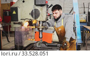 Купить «Serious young craftsman working on metal structures drilling machine in industrial workshop», видеоролик № 33528051, снято 4 августа 2020 г. (c) Яков Филимонов / Фотобанк Лори
