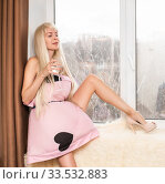 A woman dressed a pillow instead of a dress, tied with a belt drinks a drink from a glass. Стоковое фото, фотограф katalinks / Фотобанк Лори