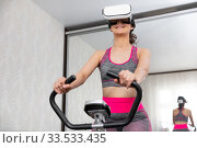 Купить «Young girl stay home in quarantine and go in for sports with virtual reality glasses. Woman exercise yoga while at home wearing virtual reality glasses», фото № 33533435, снято 4 апреля 2020 г. (c) Сергей Тимофеев / Фотобанк Лори