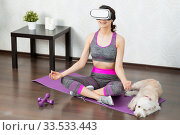 Купить «Young girl stay home in quarantine and go in for sports with virtual reality glasses. Woman exercise yoga while at home wearing virtual reality glasses», фото № 33533443, снято 4 апреля 2020 г. (c) Сергей Тимофеев / Фотобанк Лори