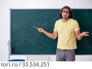 Young male student in front of blackboard. Стоковое фото, фотограф Elnur / Фотобанк Лори