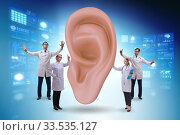 Doctor examining giant ear in medical concept. Стоковое фото, фотограф Elnur / Фотобанк Лори