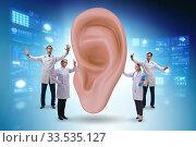 Купить «Doctor examining giant ear in medical concept», фото № 33535127, снято 16 июня 2020 г. (c) Elnur / Фотобанк Лори