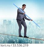 Купить «Businessman doing tightrope walking in risk concept», фото № 33536219, снято 6 сентября 2010 г. (c) Elnur / Фотобанк Лори