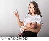 A mother breastfeeds a baby, not a bottle. Natural feeding concept. Стоковое фото, фотограф Василий Кочетков / Фотобанк Лори