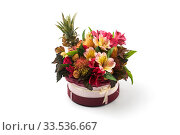 Round burgundy box filled with exotic flowers and fruits on a white background. Стоковое фото, фотограф Олег Белов / Фотобанк Лори
