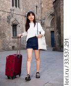 Купить «Happy young chinese tourist taking walk in city with the travel bag», фото № 33537291, снято 7 июля 2020 г. (c) Яков Филимонов / Фотобанк Лори