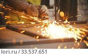 Купить «Grinding the seams of metal frame in the workshop - sparkles comes off», видеоролик № 33537651, снято 5 июня 2020 г. (c) Константин Шишкин / Фотобанк Лори