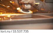 Купить «Grinding the seams of an iron frame in the welding workshop - bright sparkles», видеоролик № 33537735, снято 29 мая 2020 г. (c) Константин Шишкин / Фотобанк Лори