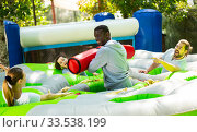Купить «Funny friends playing on an inflatable trampoline in an amusement park», фото № 33538199, снято 5 августа 2020 г. (c) Яков Филимонов / Фотобанк Лори