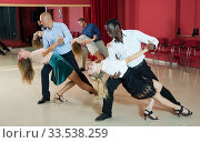 Adult pairs dancing tango movements in modern dance studio. Стоковое фото, фотограф Яков Филимонов / Фотобанк Лори