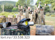 Paintball mask with splash on background with players. Стоковое фото, фотограф Яков Филимонов / Фотобанк Лори