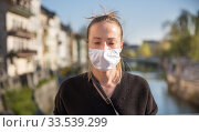 Купить «COVID-19 pandemic coronavirus. Young girl in city street wearing face mask protective for spreading of coronavirus disease 2020. Close up of young woman with medical mask on face against SARS-CoV-2», фото № 33539299, снято 8 апреля 2020 г. (c) Matej Kastelic / Фотобанк Лори