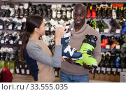 Купить «Glad woman helping African guy choose ski boots», фото № 33555035, снято 16 апреля 2019 г. (c) Яков Филимонов / Фотобанк Лори