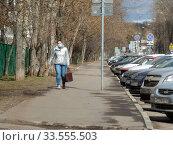 Купить «Девушка в медицинской маске идет по дороге в дни самоизоляции при коронавирусе COVID-19. Сахалинская улица. Район Гольяново. Город Москва», эксклюзивное фото № 33555503, снято 10 апреля 2020 г. (c) lana1501 / Фотобанк Лори