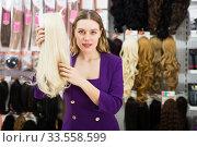 Купить «Woman selecting natural hair wigs», фото № 33558599, снято 24 февраля 2020 г. (c) Яков Филимонов / Фотобанк Лори