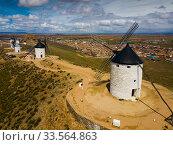Купить «Aerial view of Wind mills at knolls at Consuegra, Toledo region», фото № 33564863, снято 23 апреля 2019 г. (c) Яков Филимонов / Фотобанк Лори