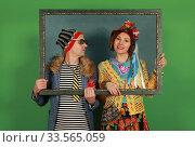 Купить «Freaky couple posing in the studio holding a picture frame in their hands», фото № 33565059, снято 12 апреля 2020 г. (c) Алексей Кузнецов / Фотобанк Лори