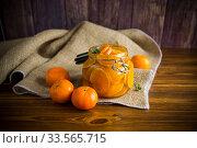 Купить «tangerine jam in a glass jar on a wooden table», фото № 33565715, снято 16 апреля 2020 г. (c) Peredniankina / Фотобанк Лори