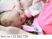 Кормление молочной смесью младенца из бутылочки. Стоковое фото, фотограф Наталья Гармашева / Фотобанк Лори