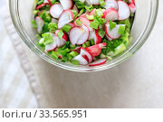 Fresh spring wholesome natural salad of radish vegetables, seasoned shallots, iceberg, romaine, cabbage in a transparent dish on the table. View from above. Стоковое фото, фотограф Tetiana Chugunova / Фотобанк Лори