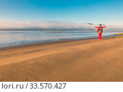 Купить «Beautiful mature woman doing gymnastics on a sandy beach on a background of autumn dawn.», фото № 33570427, снято 7 сентября 2019 г. (c) Акиньшин Владимир / Фотобанк Лори