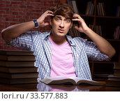 Купить «Young handsome student preparing for exams at night», фото № 33577883, снято 28 августа 2018 г. (c) Elnur / Фотобанк Лори