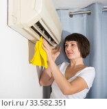 Woman dusting air conditioning. Стоковое фото, фотограф Яков Филимонов / Фотобанк Лори