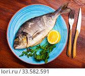Купить «Baked in oven dorado fish with orange on plate», фото № 33582591, снято 26 мая 2020 г. (c) Яков Филимонов / Фотобанк Лори