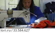 Mixed race woman using sewing machine in factory. Стоковое видео, агентство Wavebreak Media / Фотобанк Лори