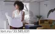 Купить «Mixed race woman looking at design in creative office», видеоролик № 33585031, снято 29 июня 2019 г. (c) Wavebreak Media / Фотобанк Лори
