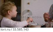 Купить «Caucasian man giving food to baby at home», видеоролик № 33585143, снято 12 апреля 2019 г. (c) Wavebreak Media / Фотобанк Лори